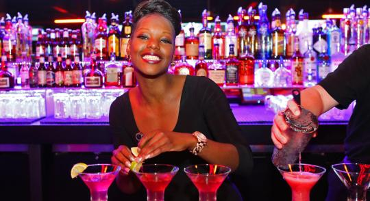 Bartender making cocktails and smiling
