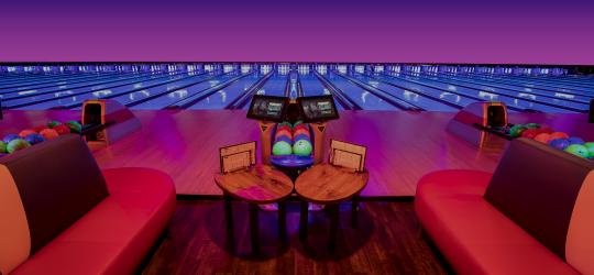 blacklight bowling lanes with plush couches