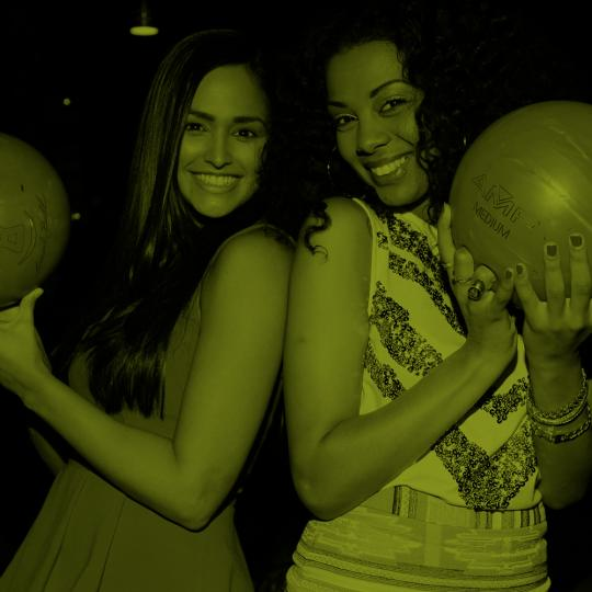two women holding bowling balls and smiling
