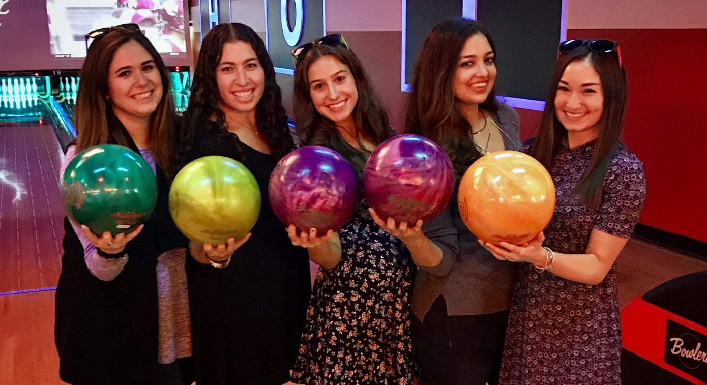 Group of women holding bowling balls