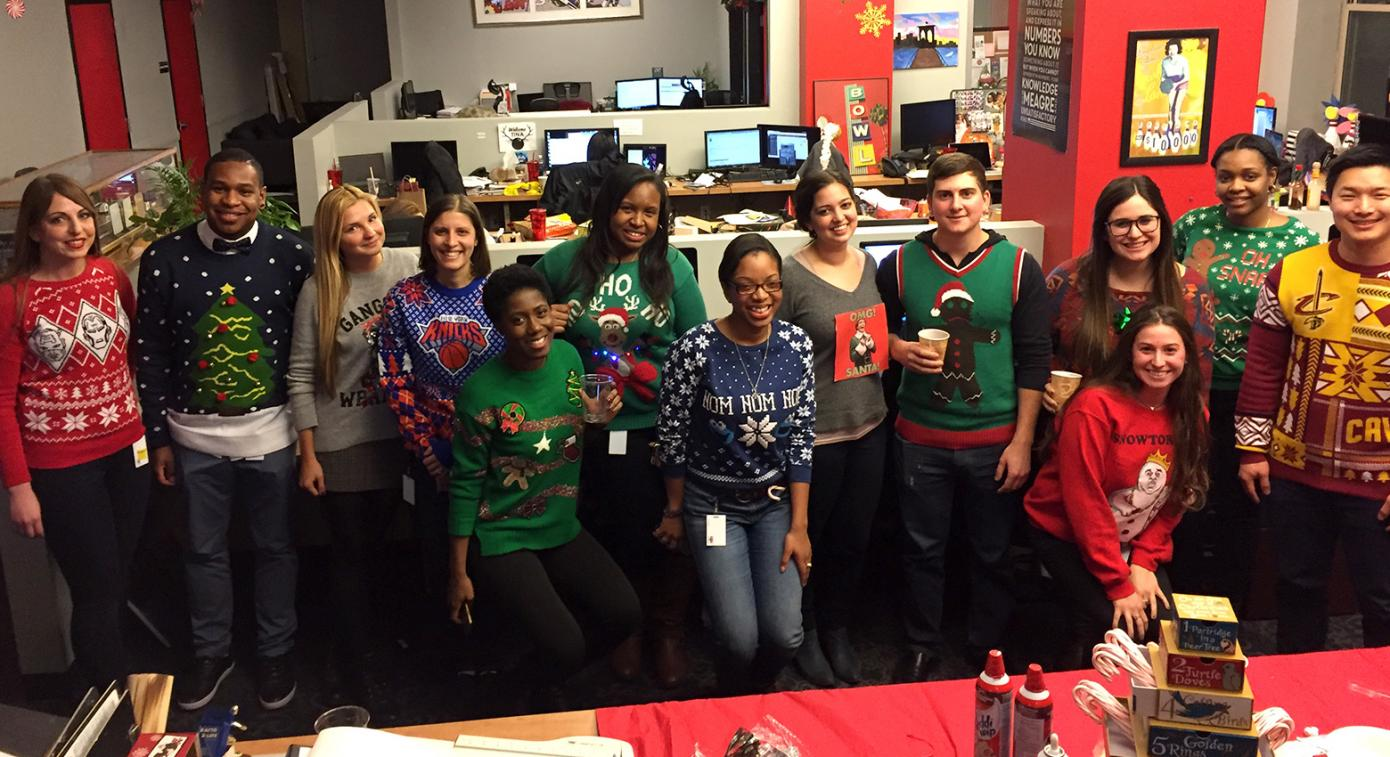 Employees wearing ugly sweaters by desks