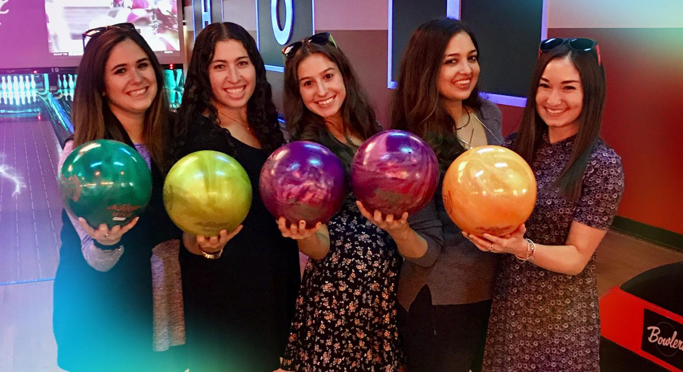 group of employees holding bowling balls